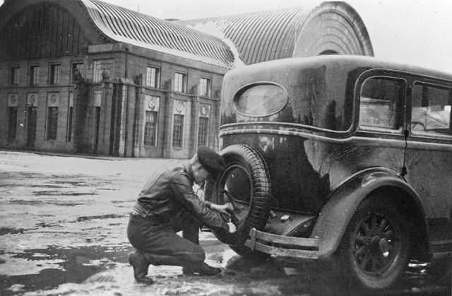 Never leave home without a Kelirengas. A taxi driver in Vyborg checking the spare tyre on his car in the 1930s.