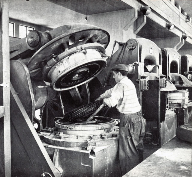 The cured tyre is lifted out of the vulcanisation press by hand.